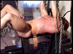 Huge bodybuilder suspended in chains and masked has balls stretched and pounded in extreme CBT video