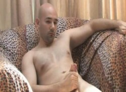 Bald guy jerking off on the sofa